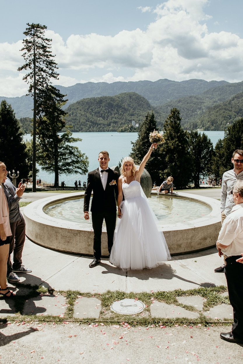 Lake Bled wedding portfolio photo of just married couple by the fountain