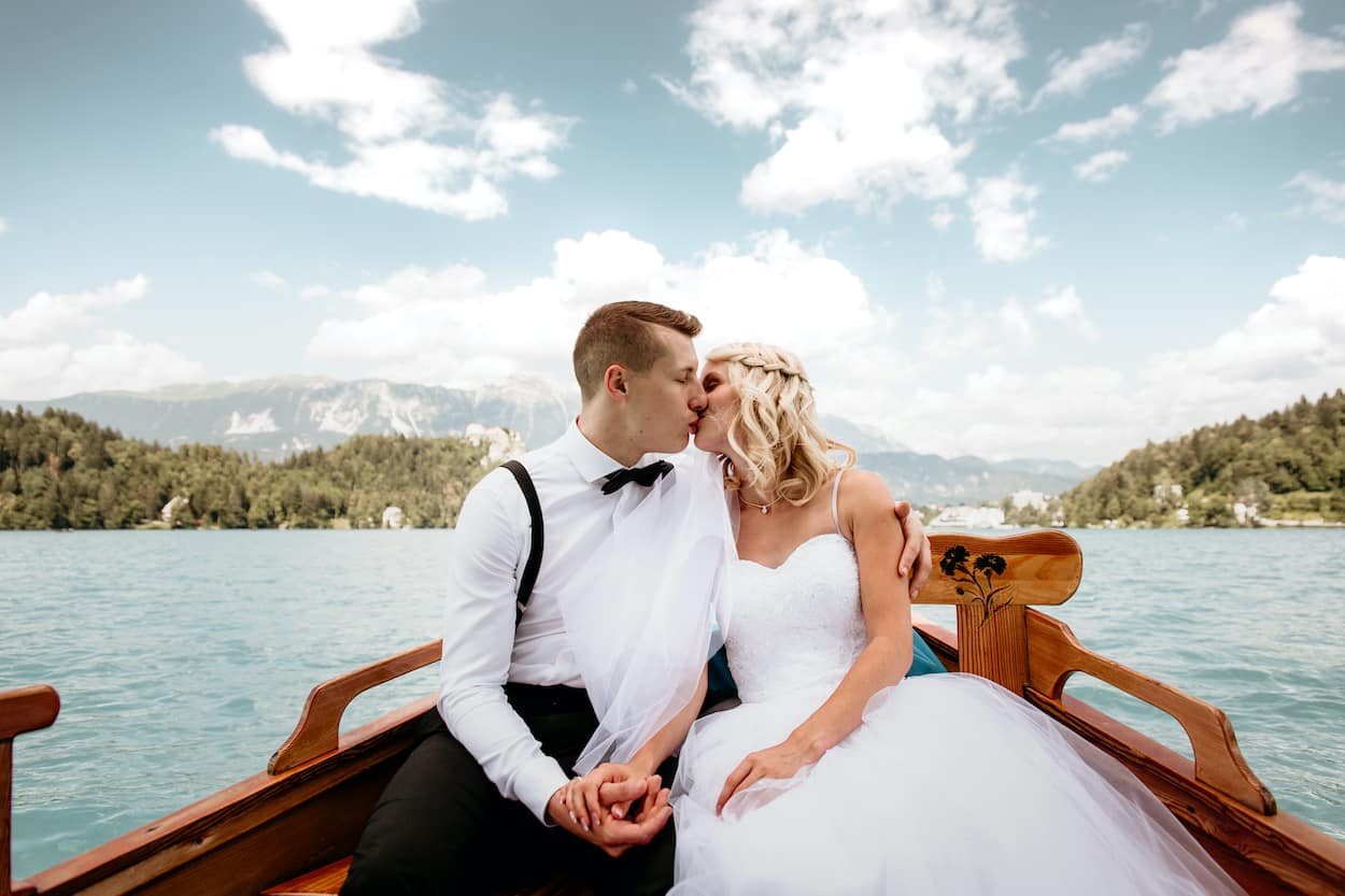 Lake Bled wedding portfolio photo of just married couple kiss on the boat