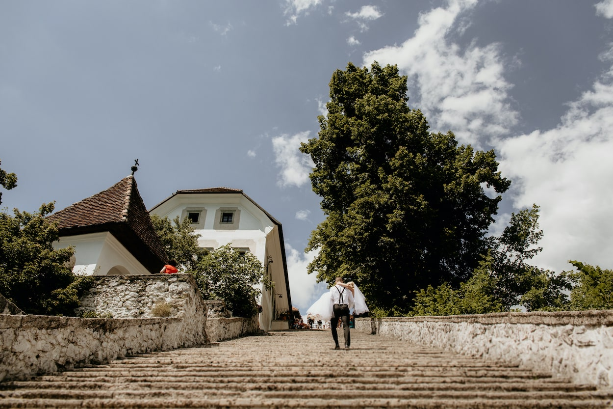 Lake Bled wedding portfolio photo of groom carrying bride up the stairs on Bled Island