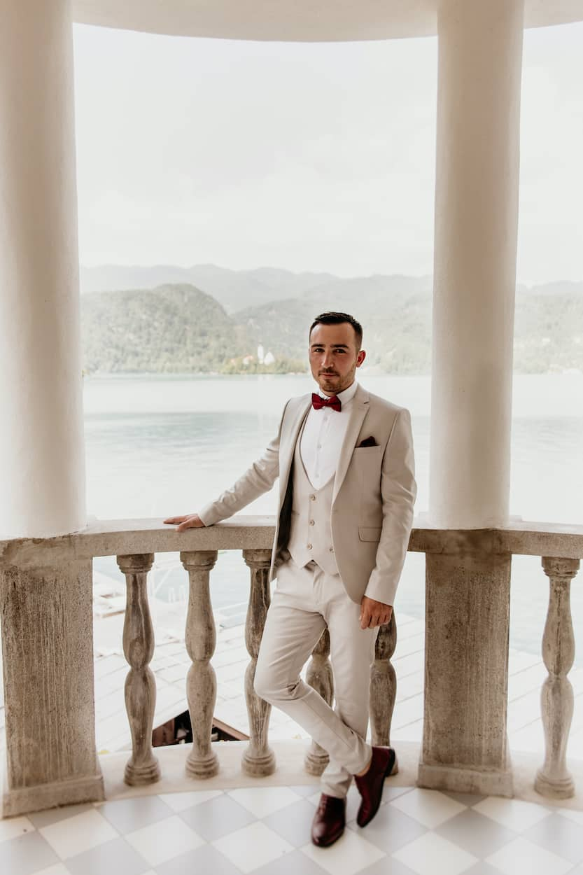 Groom posing at terrace for Lake Bled wedding portfolio
