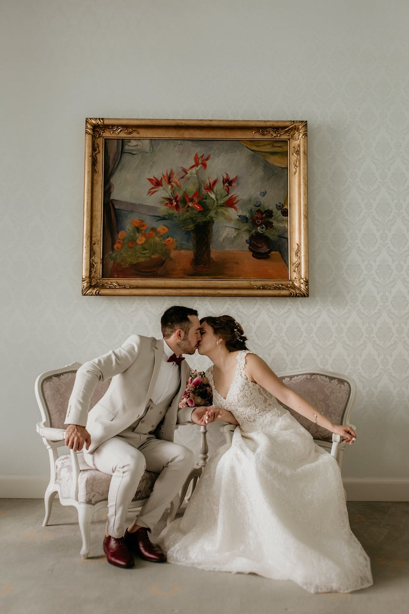 Bride and groom kissing on sofa for Lake Bled wedding portfolio
