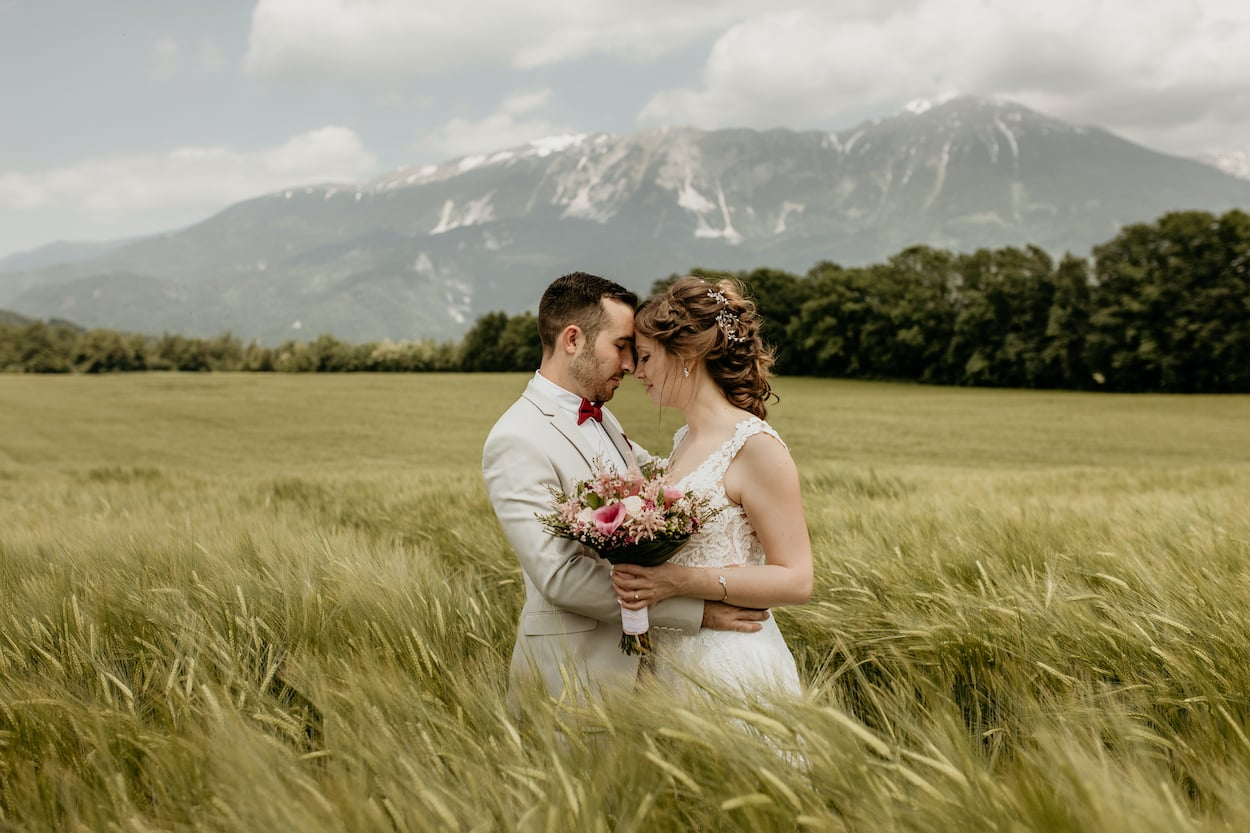 Couple hugging in the fields with bouquet for Lake Bled wedding portfolio