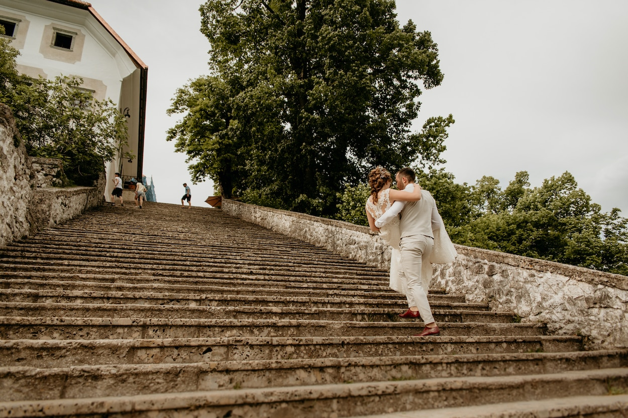 Groom carrying bride up the stairs for Lake Bled wedding portfolio