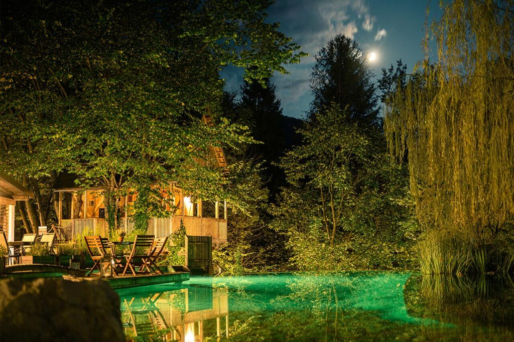 Garden Village Bled at night with green water