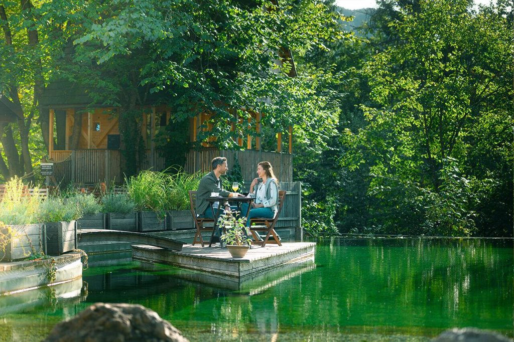Garden Village Bled couple sitting by the river