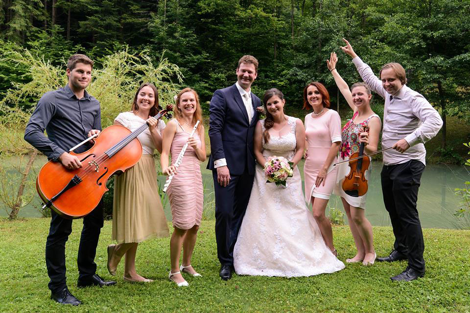 Band from Bled Wedding supplier posing with their instruments next to bride and groom