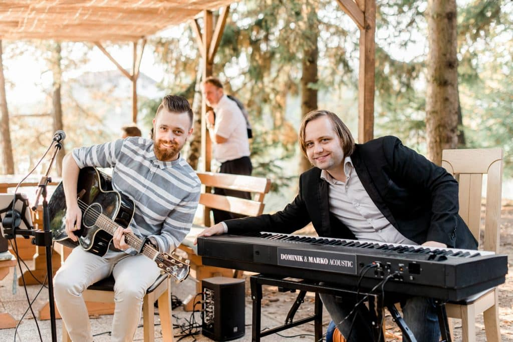 Two members of the band posing with their instruments outside at the Lake Bled Wedding