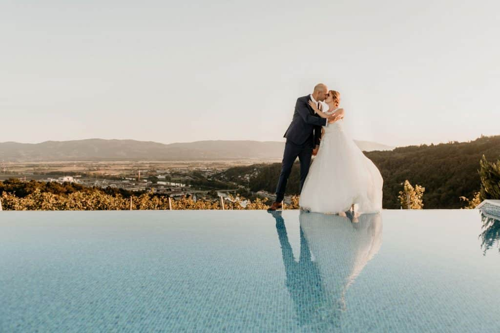 Lake Bled wedding suppliers photo of bride and groom kiss by the pool