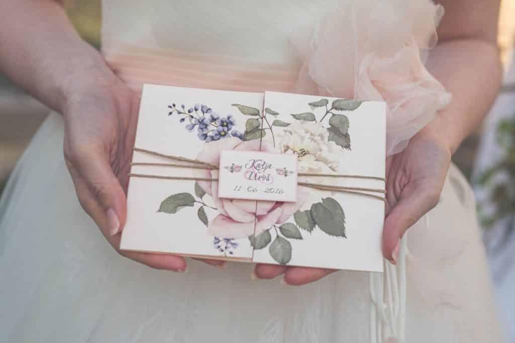 Bride holding invitation card for Wedding at Lake Bled