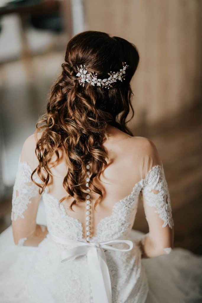 Bride shows her hair done by Lake Bled wedding supplier