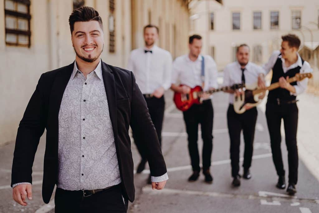 Lake Bled wedding band frontman and four members walking behind him