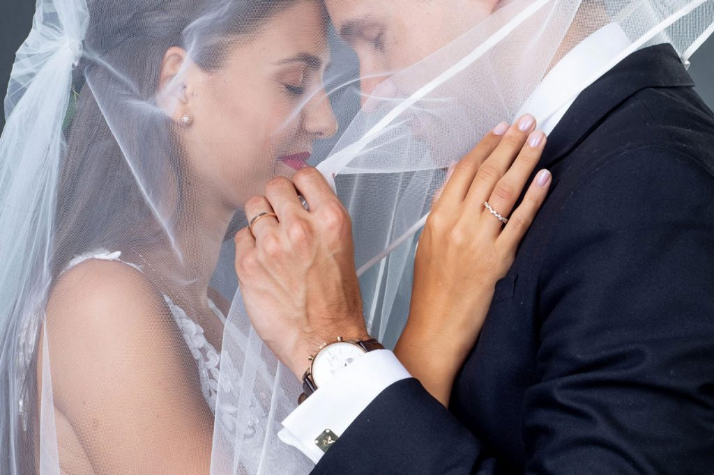 Bride and groom under the brides veil with rings from the Lake Bled wedding supplier