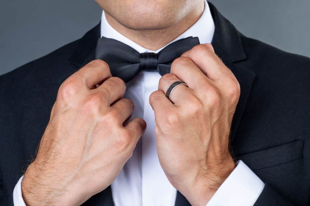 Groom adjusts his bow tie with ring on his hand by Lake Bled Wedding Supplier