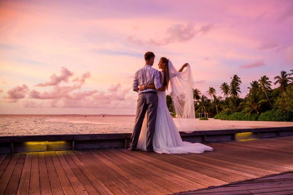 Orange pink sunset view with bride and groom by the beach