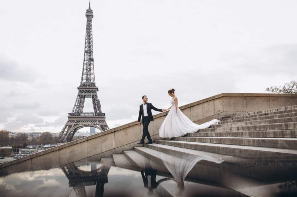 Happy married couple walking down the stirs with Eiffel tower in the background