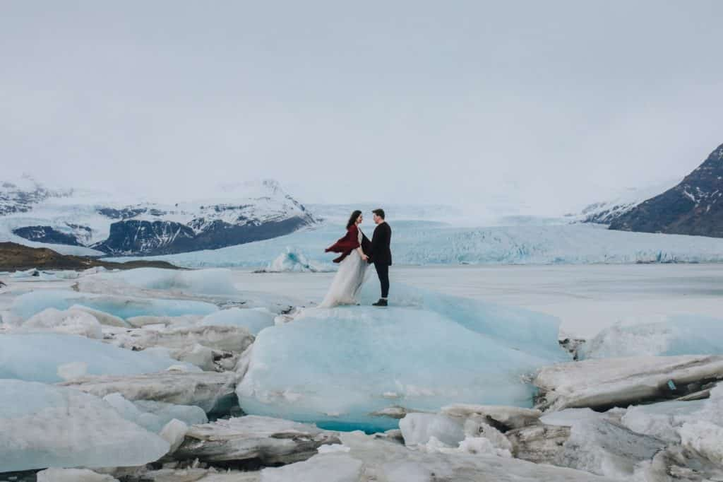 Bride and groom standing on a blue icerock in Iceland