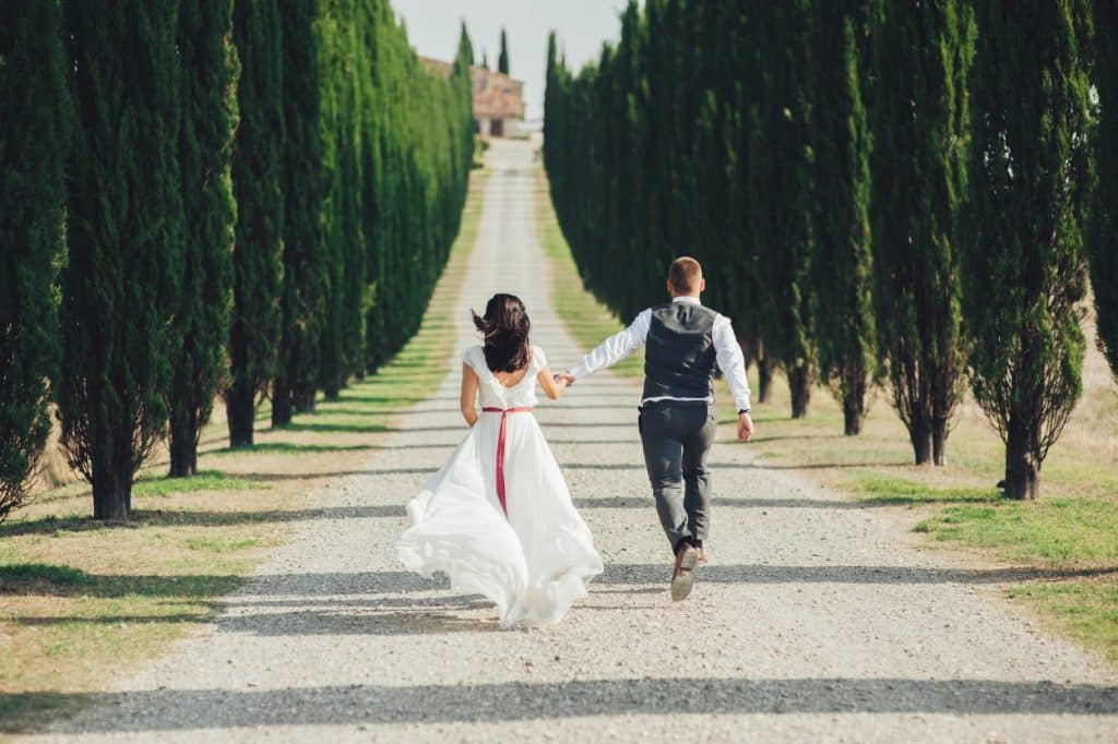 Bride and groom running in Tuscany
