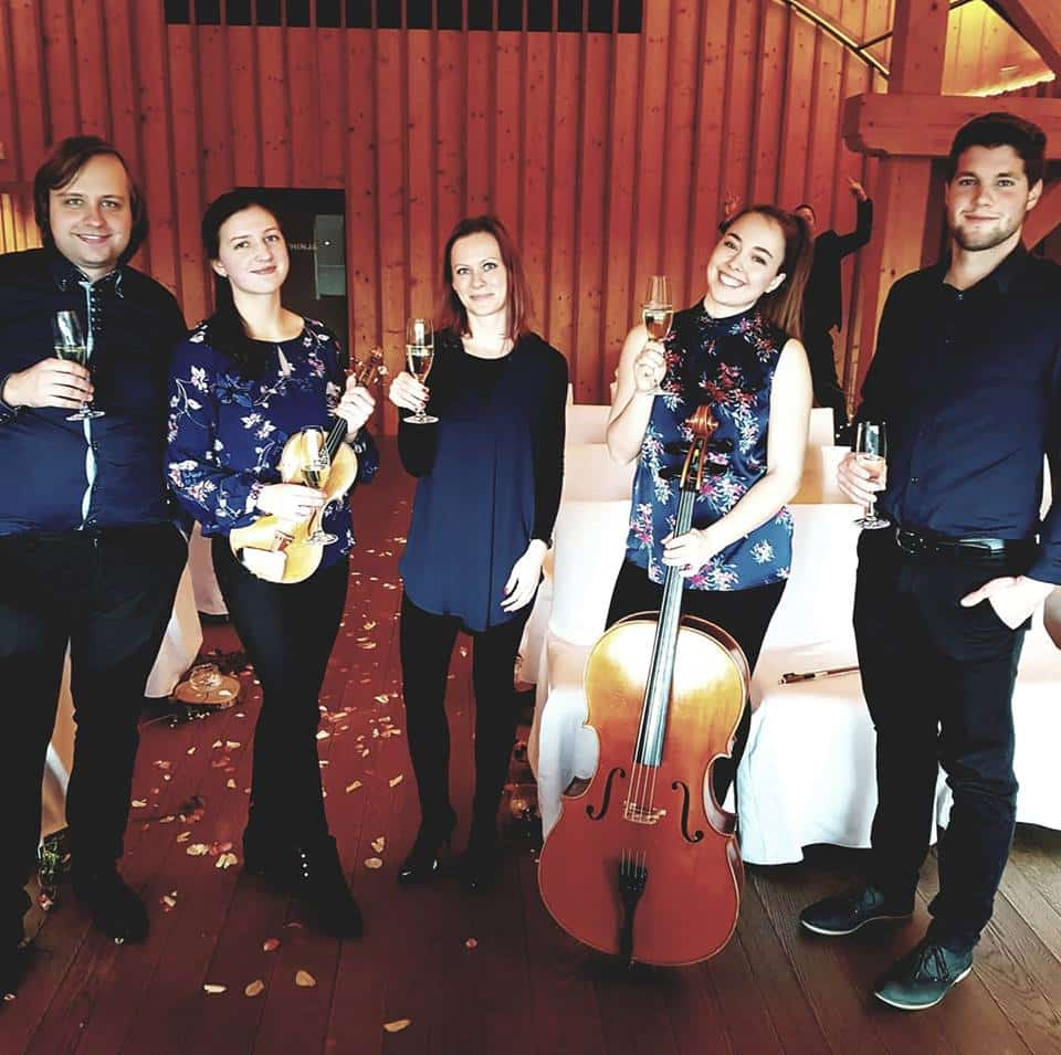 Artistik band posing together with a glass of sparkling wine