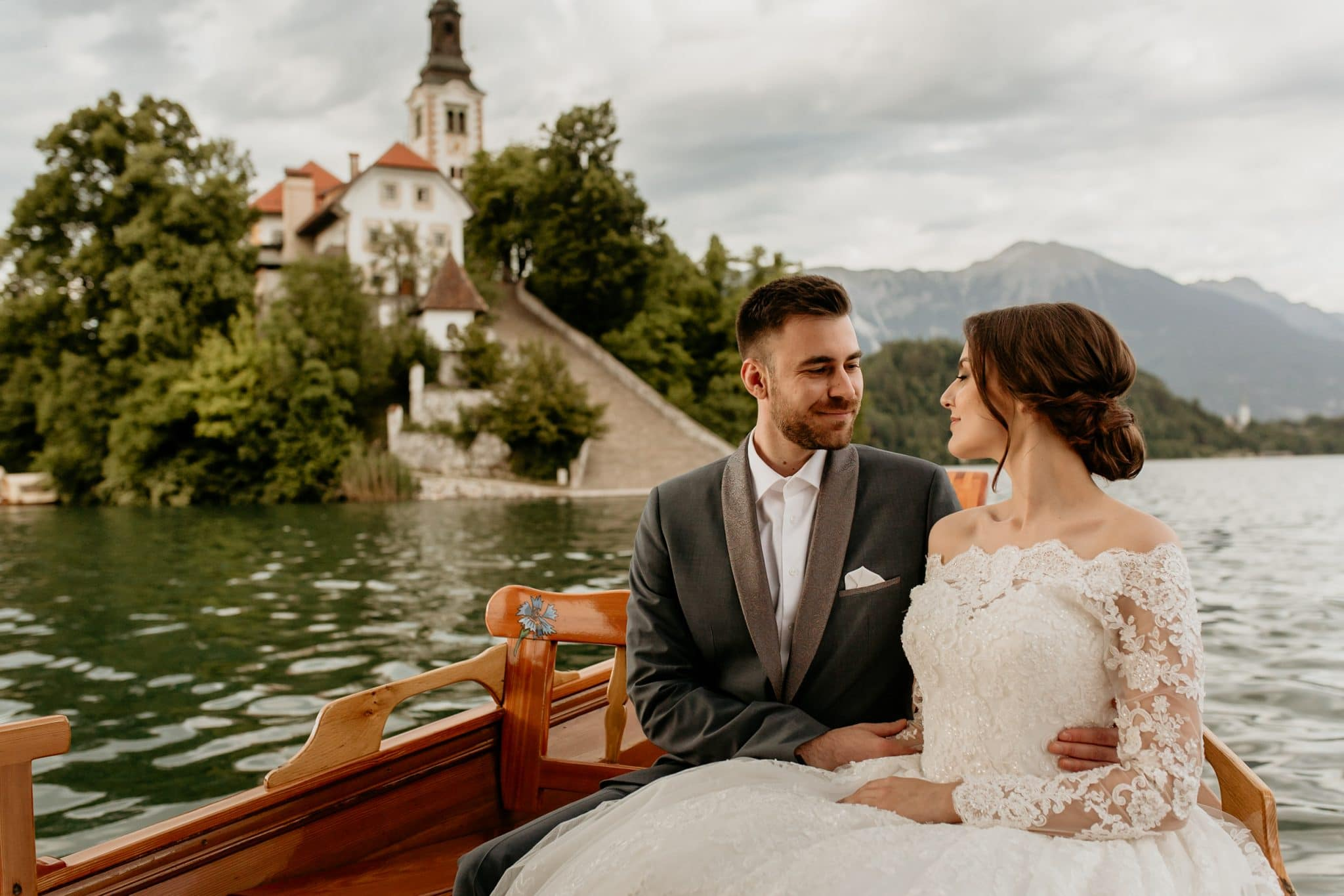 Bride and groom in pletna boat with Bled Island in the background