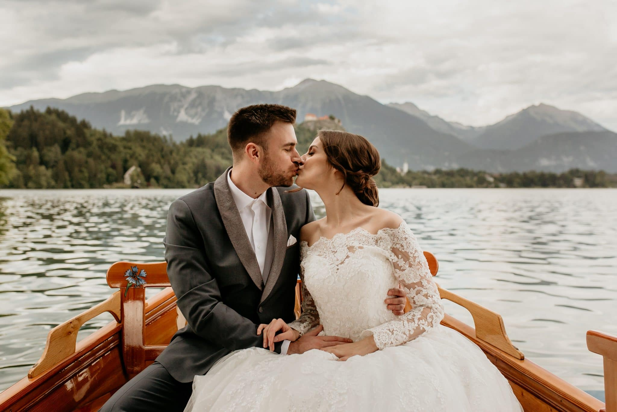 Bride and groom kiss in pletna boat at Lake Bled
