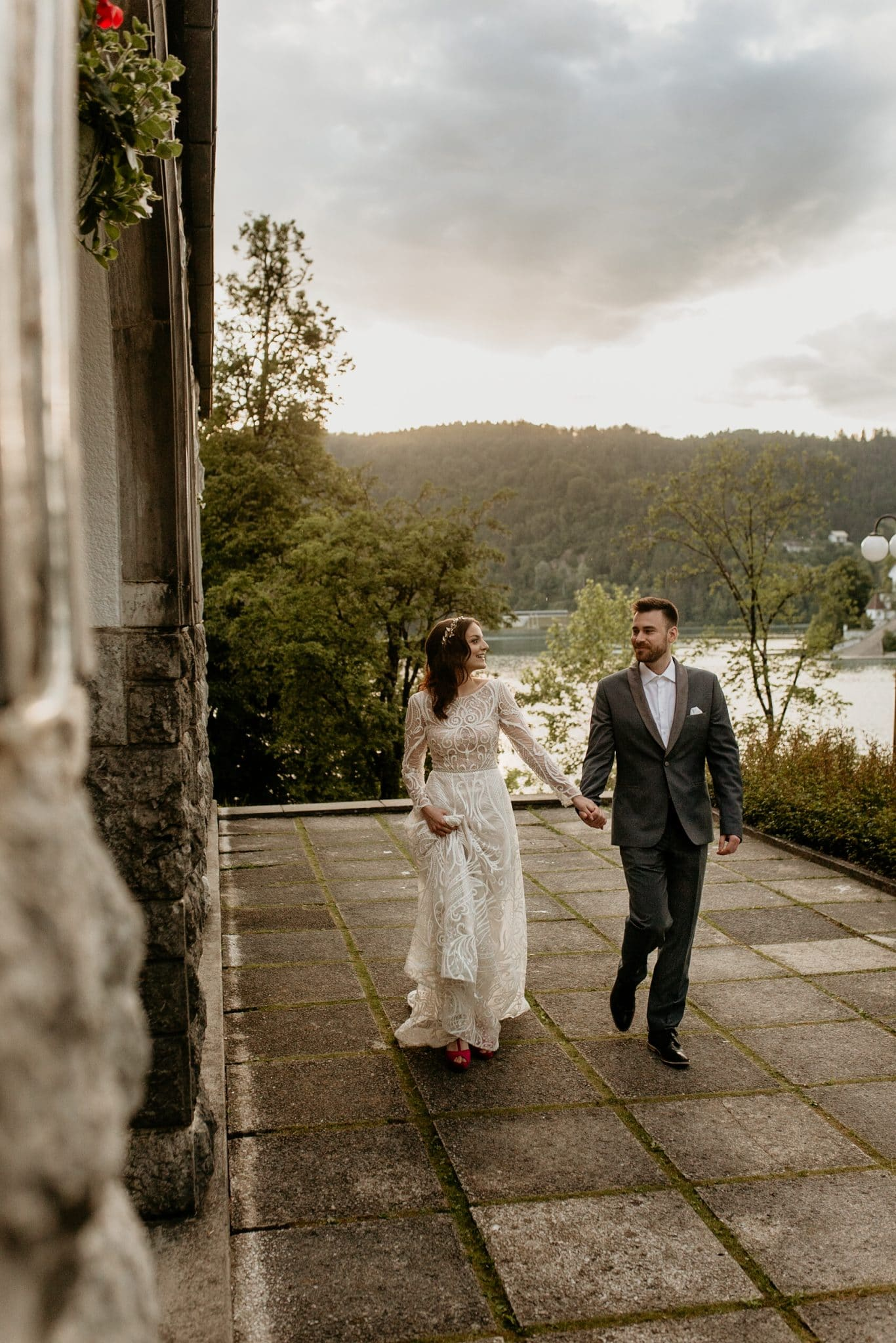 Bride and groom holding hands by Vila Bled
