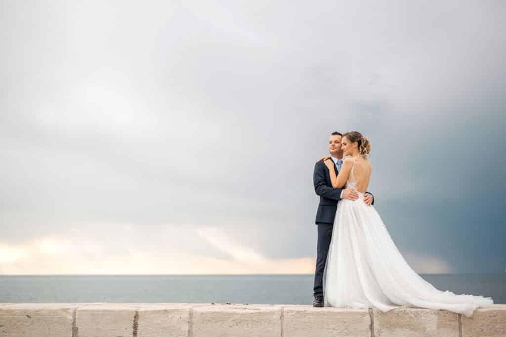 Bride and groom hug by the sea