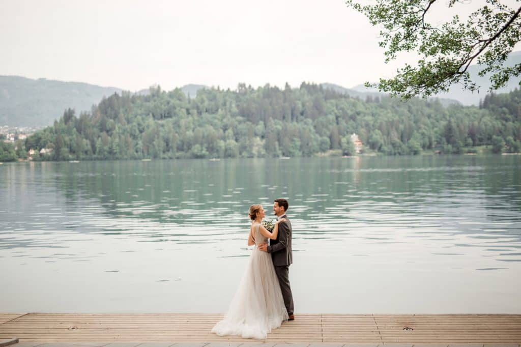 Bride and groom on the dock by the Lake Bled