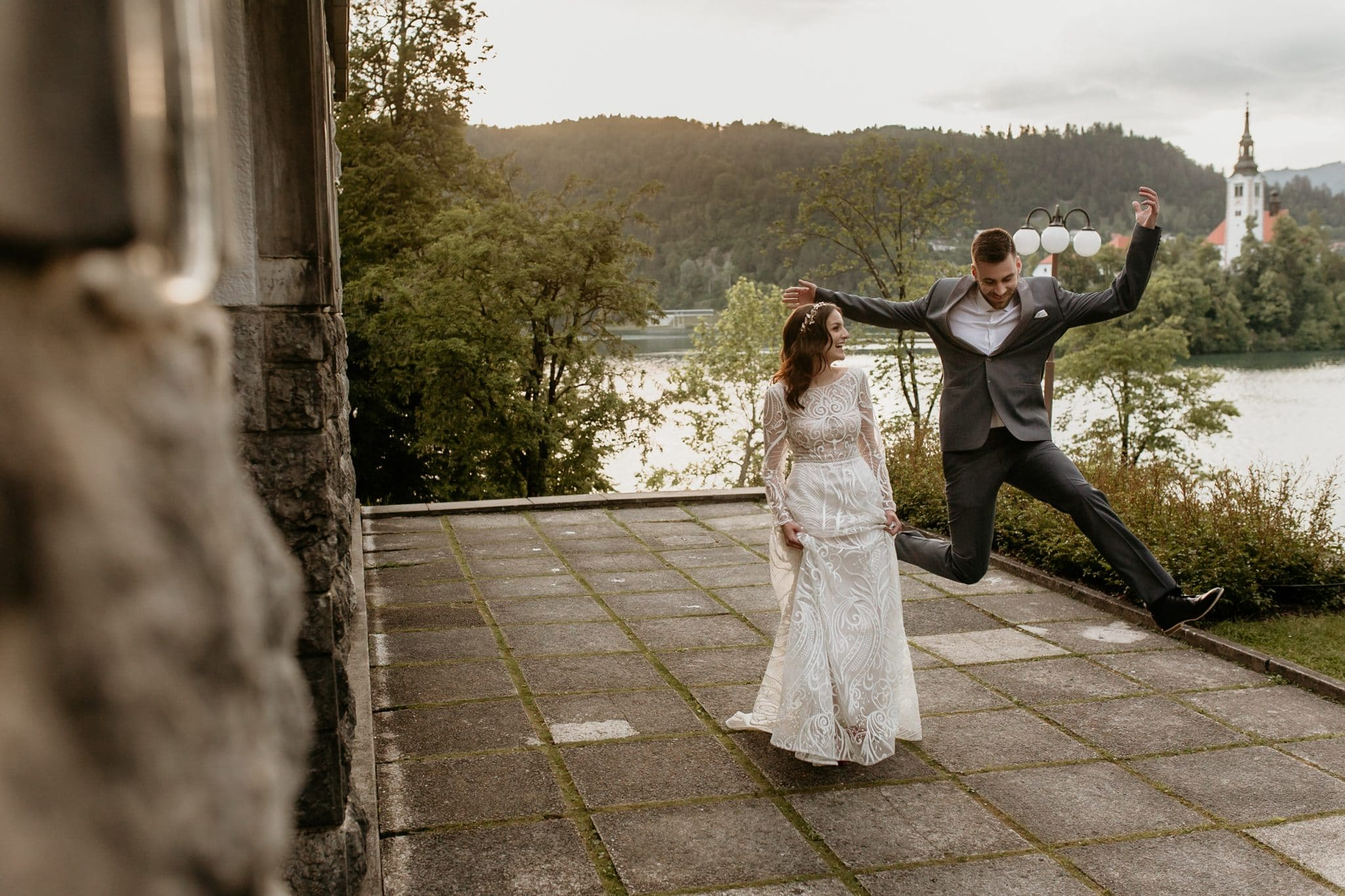 Groom jumps next to bride at Lake Bled wedding