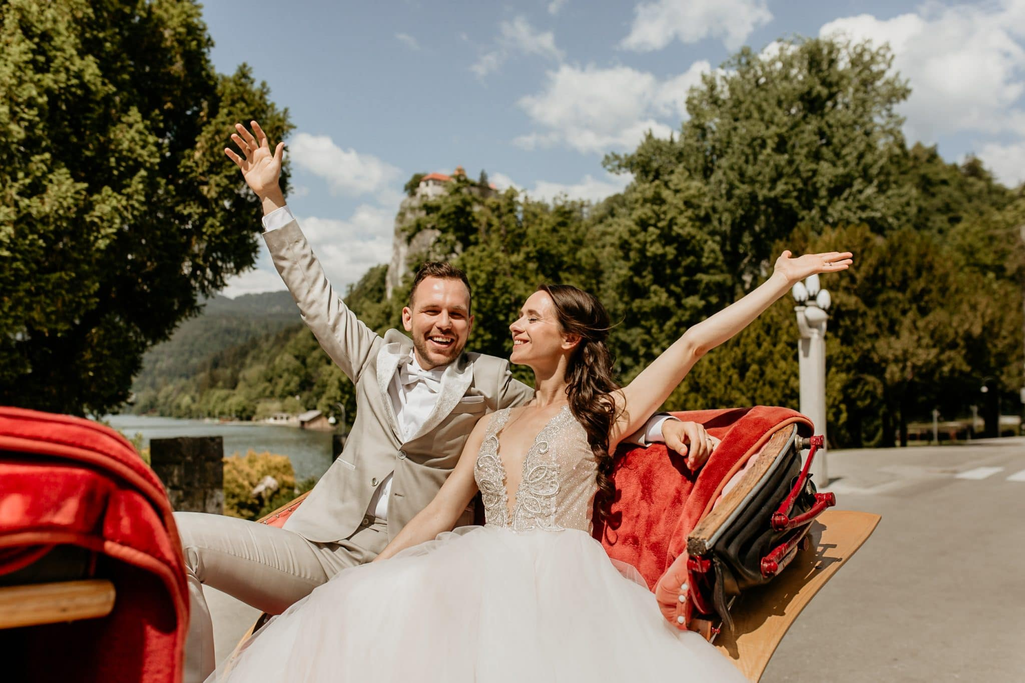 Bride and Groom spread their hands in the carriage car at Lake Bled wedding