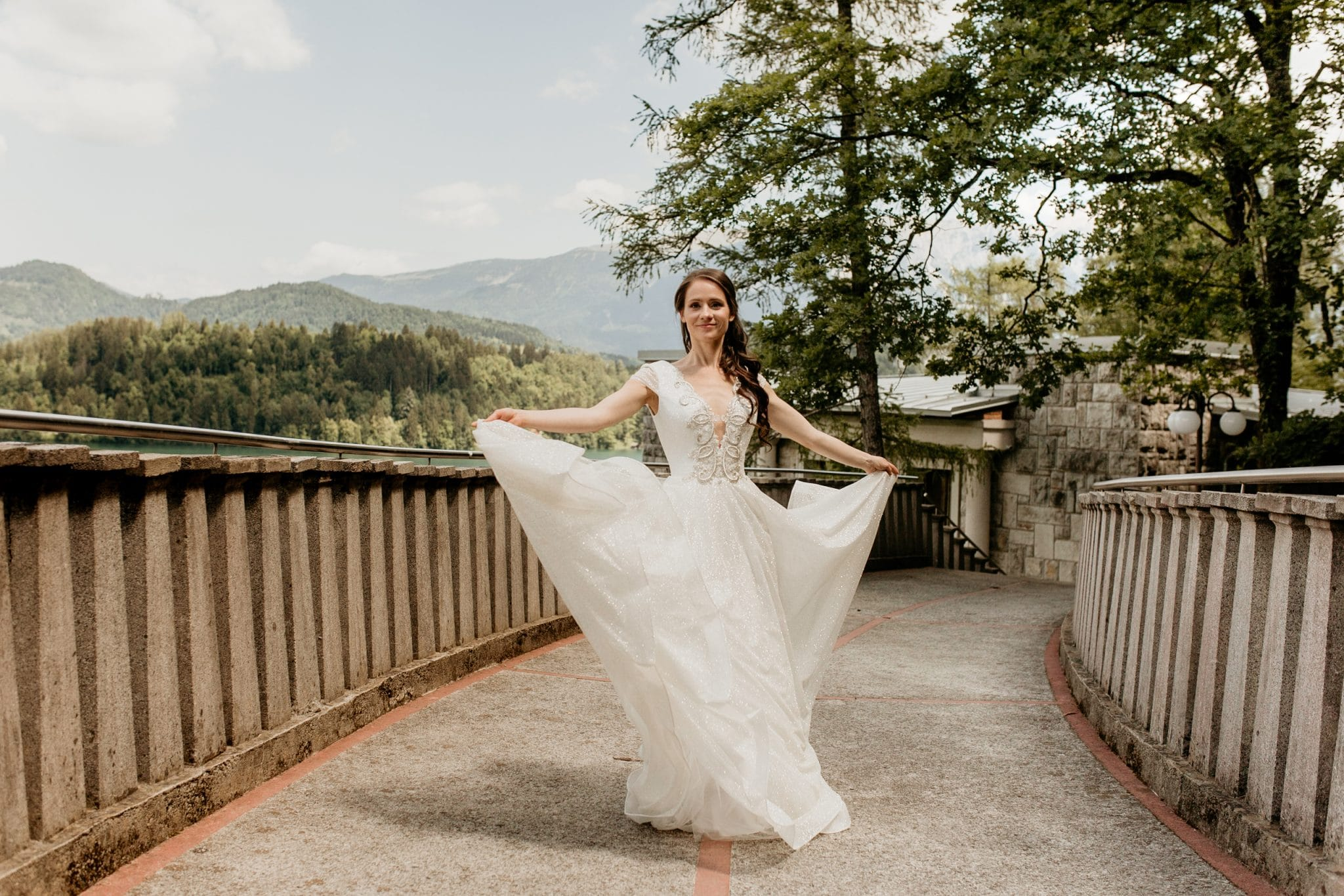 Bride at Lake Bled spreads her dress