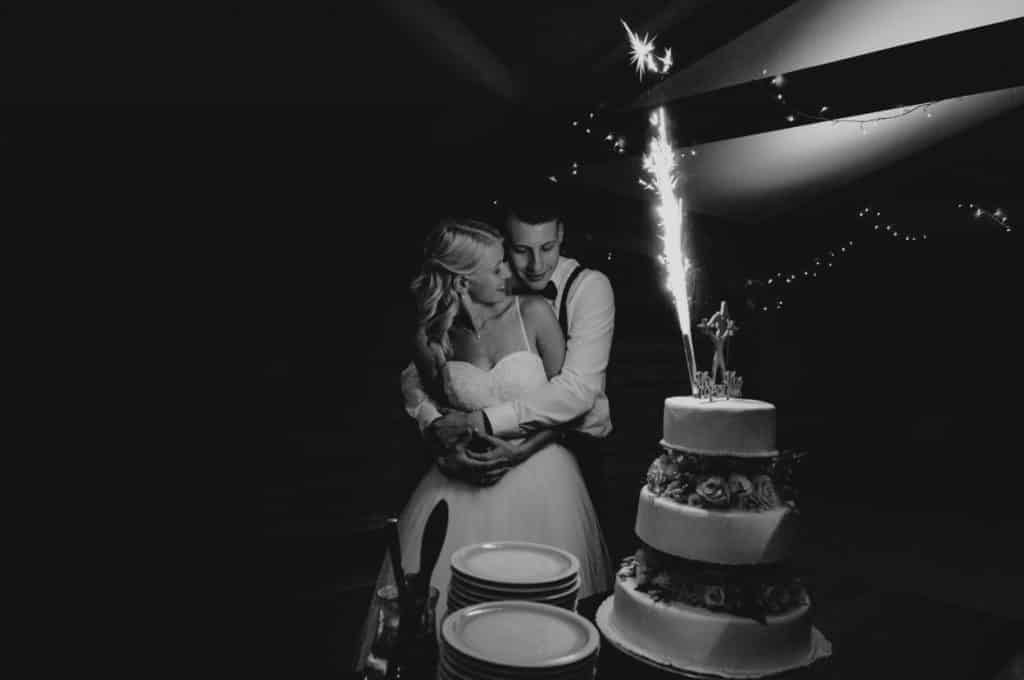 Wedding couple besides the wedding cake.