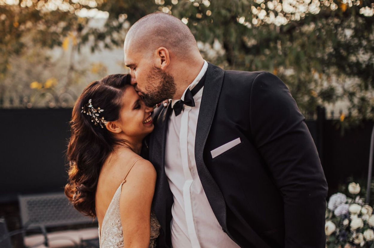 Groom kissing her bride.